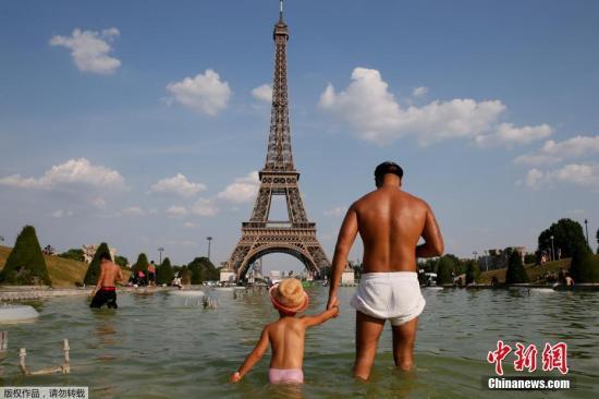 当地时间6月21日,法国巴黎,人们在埃菲尔铁塔前的TROCADERO广场上玩水,以躲避高温。