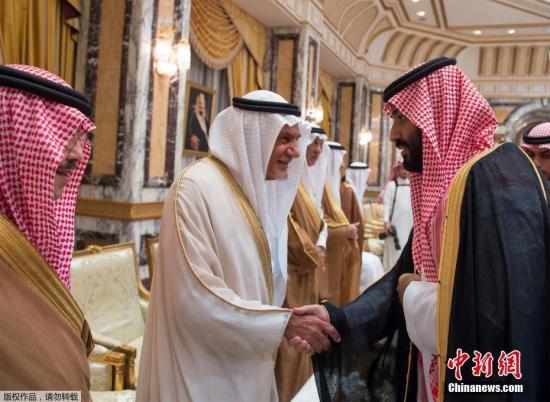 就职仪式上,穆罕默德?本?萨勒曼(右)同他人握手。