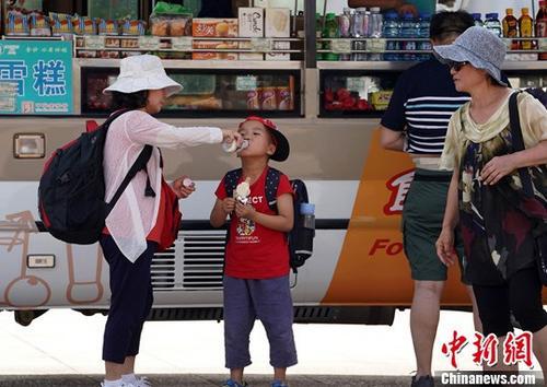 高温天气下市民喝水降温(资料图)。中新社记者 毛建军 摄