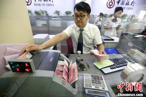 6月16日,山西太原,银行工作人员清点货币。中新社记者 张云 摄