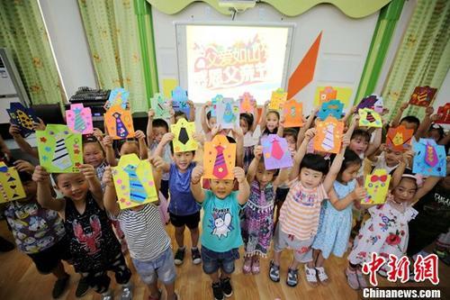 """6月16日,在河北省大厂回族自治县城区第三幼儿园,孩子们在爸爸的帮助下一起制作""""父亲节""""手工衬衫。随着6月18日""""父亲节""""临近,该幼儿园组织孩子们制作手工衬衫,送给爸爸,寓意父爱如山,表达对父爱的感恩。中新"""