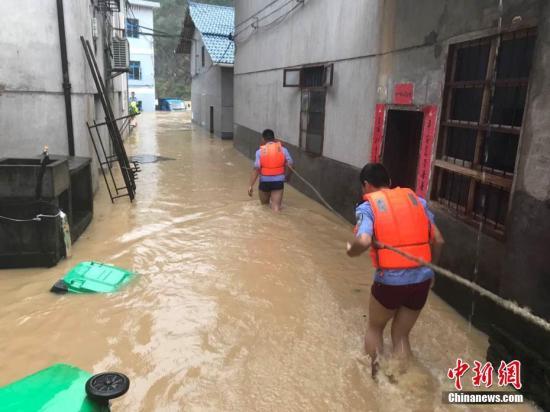图为浙江省丽水市遂昌县民警在积水中准备营救居民。