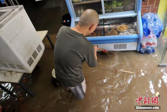 一家餐馆受涝严重,店主正在屋内进行排涝和清理垃圾。刘占昆 摄
