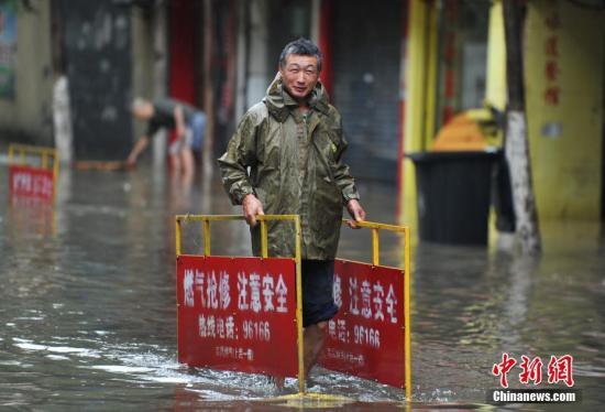 南昌市政工作人员在积水中摆放指示牌,提醒过往车辆和行人。刘占昆 摄
