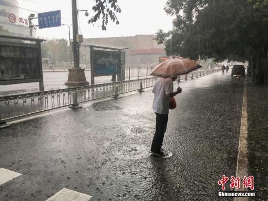图为北京阜成门,一位市民撑伞出行。 中新网记者 富宇 摄