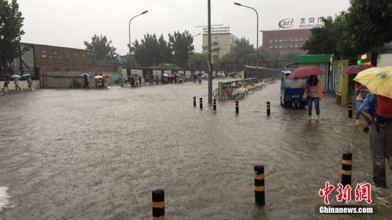 6月23日清晨,北京降雨持续,并出现了短时大雨。图为朝阳区双合家园出现积水,民众趟水出行。 中新网记者 赵姗姗 摄