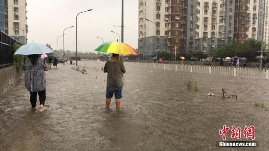 资料图:北京现大雨,民众冒雨前行。中新网记者 赵姗姗 摄