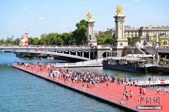 """6月23日,正在申办2024年奥运会的巴黎市政府以塞纳河和著名的亚历山大三世桥为""""舞台""""举行""""奥林匹克日""""活动,向民众推广奥运会体育项目,并组织市民参加运动体验。图为塞纳河上搭建的田径跑道。 <a target='_blank' href='http://www.chinanews.com/'>中新社</a>记者 龙剑武 摄"""