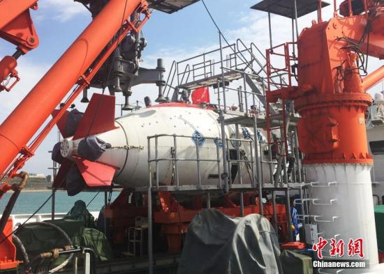 """6月23日,历时138天,航行18302海里,搭载""""蛟龙""""号载人潜水器及96名科考队员的""""向阳红09""""号船顺利返回青岛国家深海基地码头,标志着2017年""""蛟龙""""号试验性应用航次(中国大洋38航次)顺利结束。图为""""向阳红09""""号船上的""""蛟龙""""号载人潜水器。 中新社记者 阮煜琳 摄"""