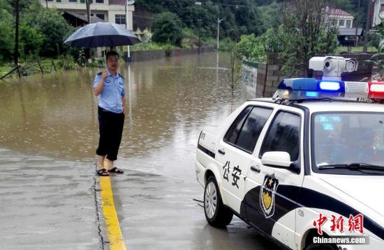 入汛以来,湖南多地先后降下暴雨。6月22日开始,湖南桃江县遭遇今年最强降雨,加之上游水库泄洪,资江桃江段水位连日来持续上涨,造成多地被洪水浸没。6月24日,桃江县警民联动,在洪水肆掠的地段,积极引导人流、车流,一道转移人员、物资,力争将洪灾损失降到最低。图为民警在危险路段值守。 王鹏 摄