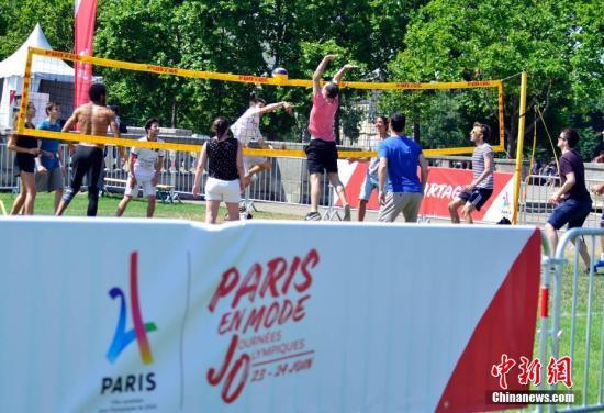"""6月23日,正在申办2024年奥运会的巴黎市政府以塞纳河和著名的亚历山大三世桥为""""舞台""""举行""""奥林匹克日""""活动,向民众推广奥运会体育项目,并组织市民参加运动体验。图为市民在塞纳河畔体验排球运动。 <a target='_blank' href='http://www.chinanews.com/'>中新社</a>记者 龙剑武 摄"""