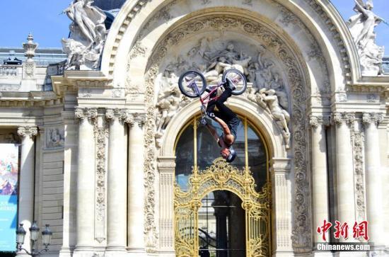 """6月23日,正在申办2024年奥运会的巴黎市政府以塞纳河和著名的亚历山大三世桥为""""舞台""""举行""""奥林匹克日""""活动,向民众推广奥运会体育项目,并组织市民参加运动体验。图为自行车运动爱好者为市民表演飞车特技。 <a target='_blank' href='http://www.chinanews.com/'>中新社</a>记者 龙剑武 摄"""