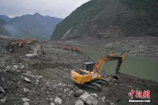 6月25日,大型机械在垮塌现场作业。 中新社记者 刘忠俊 摄