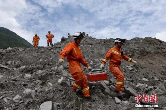 6月25日,消防官兵抬生命探测仪搜寻幸存者。 姜学华 摄