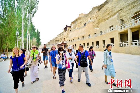 图为6月24日,国内外旅行商考察团在敦煌莫高窟参观考察。 王斌银 摄