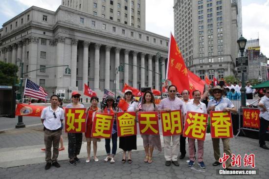 """当地时间6月25日,美东各界华侨华人庆祝香港回归二十周年大会在纽约曼哈顿弗利广场举行。图为参会华人华侨打出""""香港明天会更好""""标语。<a target='_blank' href='http://www.chinanews.com/'>中新社</a>记者 廖攀 摄"""