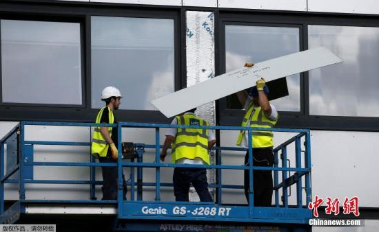 当地时间2017年6月26日,英国伦敦,工人们拆除大楼上的不防火外层材料。英政府25日宣布,英格兰共有60栋高楼未通过消防测试。保险业协会则表示,先前早就提醒过有关官员,外墙材质可能造成火势蔓延。