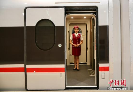 """6月26日,在北京南站等待首发的""""复兴号""""高铁动车组乘务员迎接乘客到来。记者 翟璐 摄"""