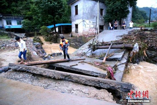 资料图 灾区学生爬梯攀上被水毁的桥梁才能到寄宿的学校上学。黄一魏 摄