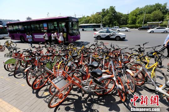 """资料图:公交站周围的共享单车""""挤作一团""""。 张远 摄"""