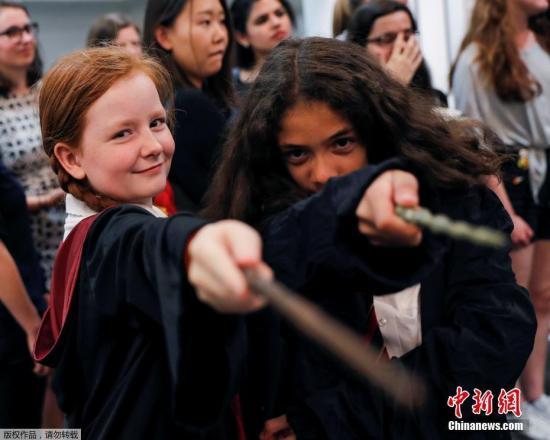"""2017年6月26日,是风靡世界的魔幻小说《哈利?波特》首部《哈利?波特与魔法石》出版20周年的日子,英国各地""""哈迷""""们举行庆祝活动,为了纪念这个""""魔法世界""""诞生20周年。图为当地时间6月26日,在伦敦Waterstones书店,""""哈迷""""们身穿长袍,手执哈利的魔杖和老魔杖。"""