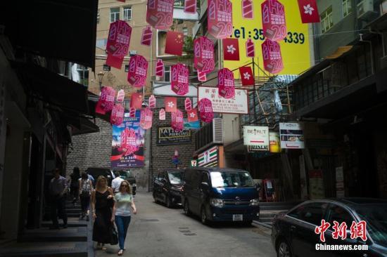 6月27日,香港兰桂坊,商家悬挂旗帜宣传其香港回归20周年派对活动。 中新社记者 盛佳鹏 摄
