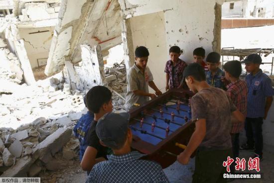 當地時間2017年6月26日,敘利亞反對派控制區杜馬,男孩在廢棄的建築內玩桌上足球慶祝開齋節。