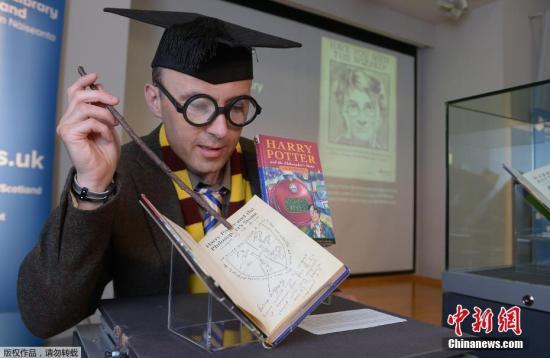 """2017年6月26日,是风靡世界的魔幻小说《哈利?波特》首部《哈利?波特与魔法石》出版20周年的日子,英国各地""""哈迷""""们举行庆祝活动,为了纪念这个""""魔法世界""""诞生20周年。图为一名""""哈迷""""在对着J.K.罗琳手写笔记""""施魔法""""。"""