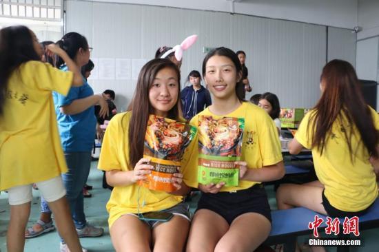 两名美国华裔青少年手捧袋装螺蛳粉合影。 林馨 摄