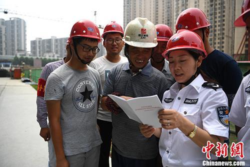 资料图:安监办工作人员进工地给农民工普及安全生产知识。中新社记者 韩苏原 摄