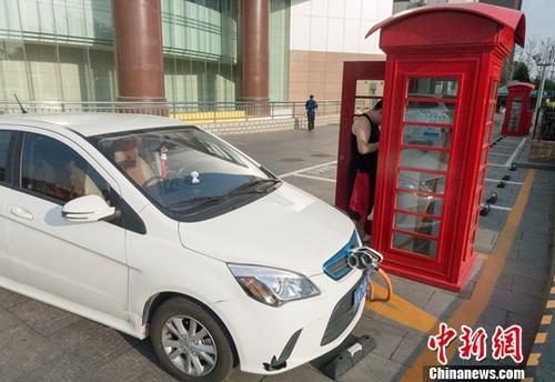 6月10日,北京,一位电动汽车车主正操作充电桩给车辆充电,该充电桩的外观被设计成类似英国伦敦街头的经典红色公用电话亭,别具特色。中新社记者 侯宇 摄