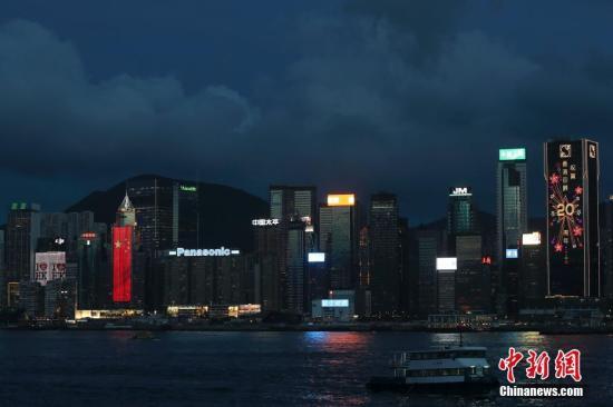 """香港回归祖国二十周年庆典临近,香港庆回归气氛渐浓,6月27日晚,在维多利亚港湾两侧霓虹闪烁,大厦上的电子屏""""升起""""巨幅五星红旗和紫荆花区旗,交替展现,并有""""热烈庆祝香港回归祖国20周年""""、""""祝贺香港回归20周年""""字样。 <a target='_blank' href='http://www.chinanews.com/'>中新社</a>记者 盛佳鹏 摄"""