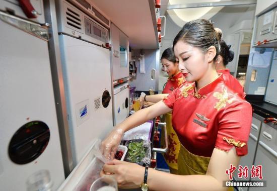 资料图:空姐在机舱里准备餐食。王东明 摄