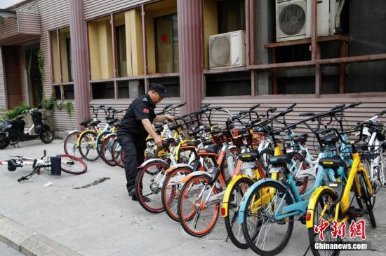 资料图:在杭州,保安把共享单车摆放整齐。 <a target='_blank' href='http://www.chinanews.com/'>中新社</a>记者 王远 摄