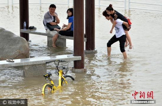 2017年6月29日,在武汉市武昌黄花矶,市民在江水漫过的亲水平台上玩耍。股票网 来源:视觉中国