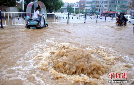 江西省瑞昌市黄金北路的两处下水道井盖被暴雨冲开,积水喷涌而出。魏东升 摄