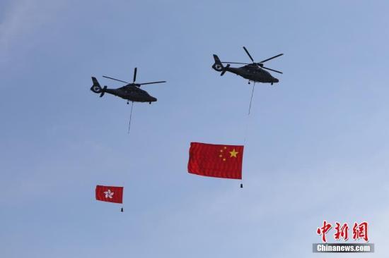 7月1日,香港特区政府在金紫荆广场举行升旗仪式,庆祝香港回归祖国20周年。图为两架分别悬挂中华人民共和国国旗、香港特区区旗的直升机从空中飞过。<a target='_blank' href='http://www.chinanews.com/'>中新社</a>记者 谢光磊 摄