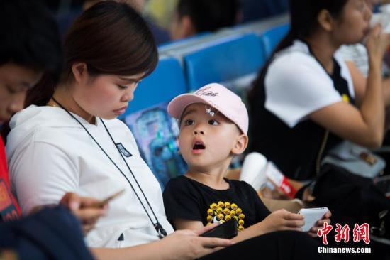 母子一同玩手机,消磨时间。李南轩 摄