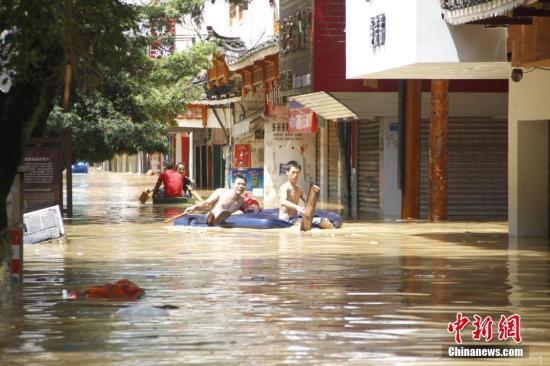 7月2日,因连日暴雨,位于珠江上游的融江河水猛涨,导致广西柳州市融水苗族自治县县城一半城区被泡,街道成河,居民只得乘船出行。朱柳融 摄