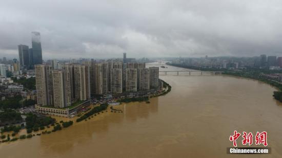 7月3日,因受连日暴雨影响,广西柳江河柳州段出现超警戒水位。洪水导致沿江低洼地带被淹,柳州呈现洪水围城的情景,城市在洪水中如同孤岛。当天4时50分许,柳江柳州水文站出现85.56米左右的洪峰水位(警戒水位82.5米)。连日来广西多地遭遇大到暴雨袭击,强降雨造成部分河流超警戒水位。图为航拍柳州市柳江河面和被洪水淹没沿江路段。 王以照 摄