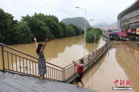 7月3日,受连日强降雨影响,广西柳州市区柳江河水位暴涨,部分沿江路段被洪水淹没。当天4时50分许,柳江柳州水文站出现85.56米左右的洪峰水位(警戒水位82.5米)。当地民众在洪水里划皮划艇放网捕鱼、自拍、洗车。目前,洪峰已过境,柳江柳州市区水位在不断下降。图为当地民众在被洪水淹没路段拍照。 林馨 摄