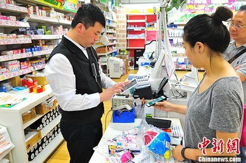 """7月3日,在东京著名繁华街区涩谷的一家商店内,顾客尝试用来自中国企业的""""扫码支付""""付款。 中新社记者 吕少威 摄"""