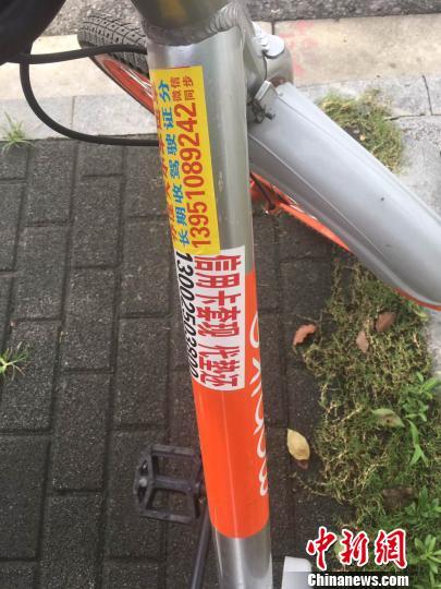 """资料图:粘贴在共享单车上的各种""""牛皮癣""""小广告。朱晓颖 摄"""