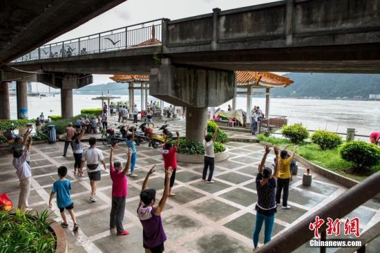 """资料图:广西梧州 """"大妈""""河边秀广场舞。陈选平 摄"""