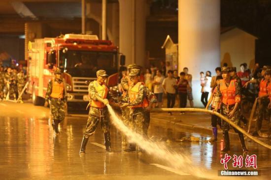 武警官兵在沿江被淹路段展开清淤。王伟 摄