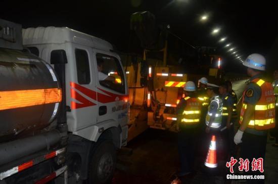 拖车把事故油罐车拖离隧道。刘刚 摄