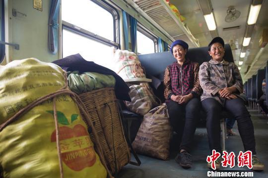 """资料图:穿行大凉山的""""扶贫列车""""。在普雄开往攀枝花的5633次列车上,两名到喜德贩卖土豆的彝族妇女正守护着自己的货品。 龚萱 摄"""