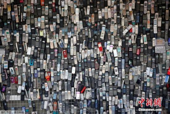 资料图:一家经营电子产品的商店,满满一墙的老手机是店主20年来的收藏成果。
