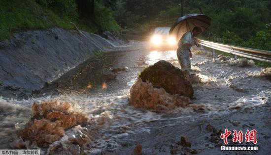 """当地时间2017年7月5日,台风""""南玛都""""为日本九州地区带来强降雨。图为九州岛大分县,大雨导致巨石滚落,交通瘫痪。"""