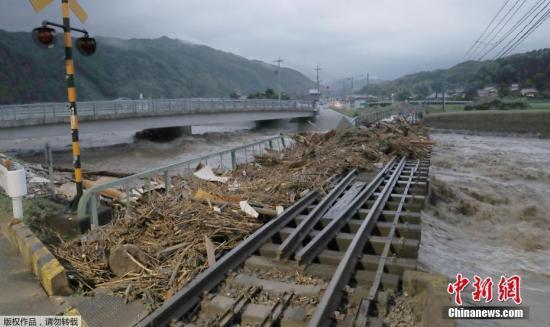 """台风""""南玛都""""4日吹袭日本,挟着时速144公里强风,在九州岛东南部的长崎登陆,随后九州岛交通陷于瘫痪。图为九州岛福冈县,洪水过后,铁道上堆满了木屑和垃圾。"""